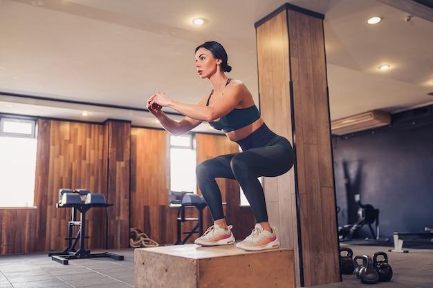 Ujęcie młodej kobiety poćwiczyć z pudełkiem na siłowni