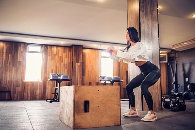 Ujęcie młodej kobiety, poćwiczyć z pudełkiem na siłowni