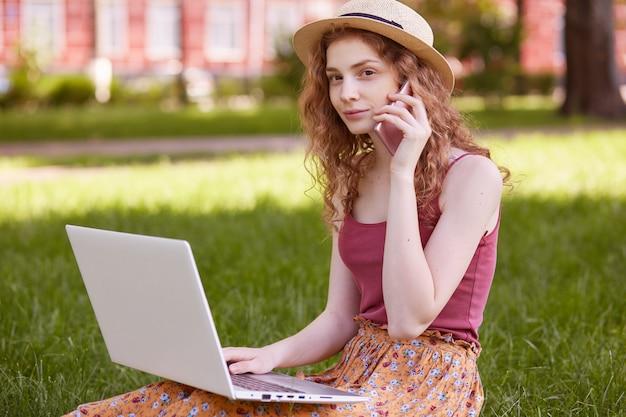 Ujęcie młodej kobiety w kapeluszu, siedzącej na zielonej trawie i używającej laptopa do edukacji online w parku, prowadzi rozmowę ze swoim nauczycielem przez inteligentny telefon, patrząc na bok podczas komunikowania się, pozować na zewnątrz.