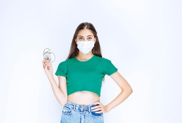 Ujęcie młodej kobiety w masce medycznej pokazując budzik.