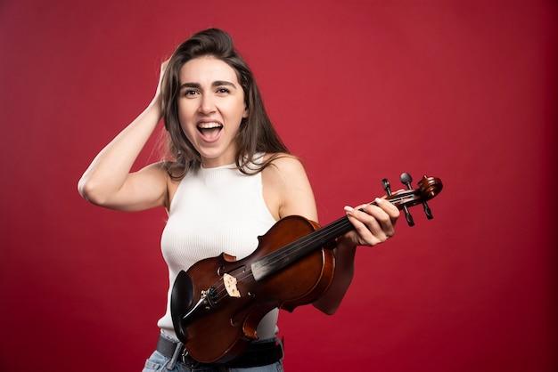 Ujęcie młodej modelki trzymającej skrzypce na lekcję muzyki