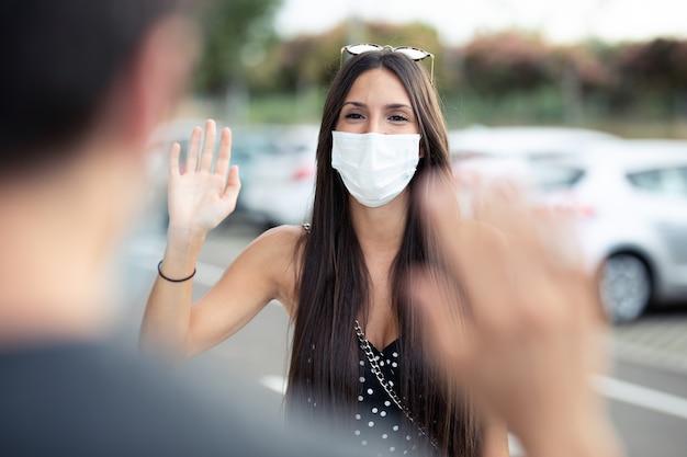 Ujęcie młodej pięknej kobiety studentki noszącej maskę chirurgiczną i machając ręką na powitanie jej przyjaciela w kampusie uniwersyteckim w epidemii covid19. dystans społeczny i nowa koncepcja normalności.