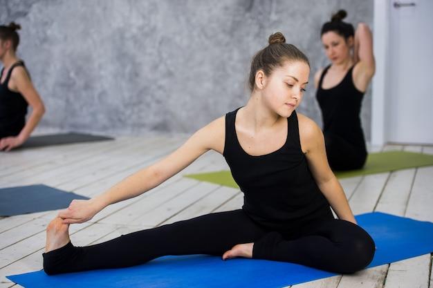 Ujęcie młodych kobiet rozgrzewki przed sesją jogi
