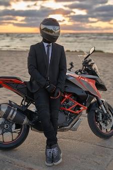 Ujęcie motocyklisty ubranego w czarny kostium i kask pozujący ze swoim motocyklem na plaży.