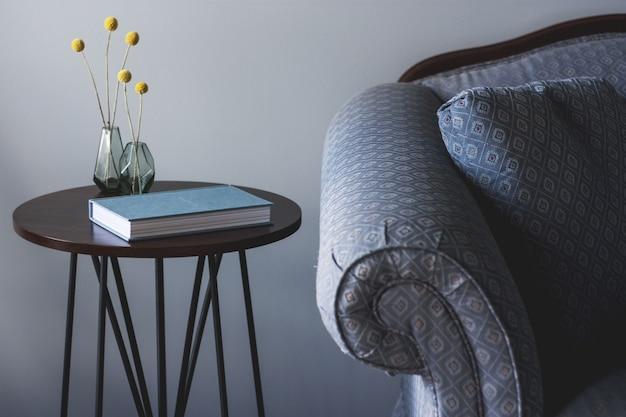 Ujęcie niebieskiej kanapy w pobliżu małego okrągłego stołu z książką i dwoma wazami z żółtymi roślinami na nim