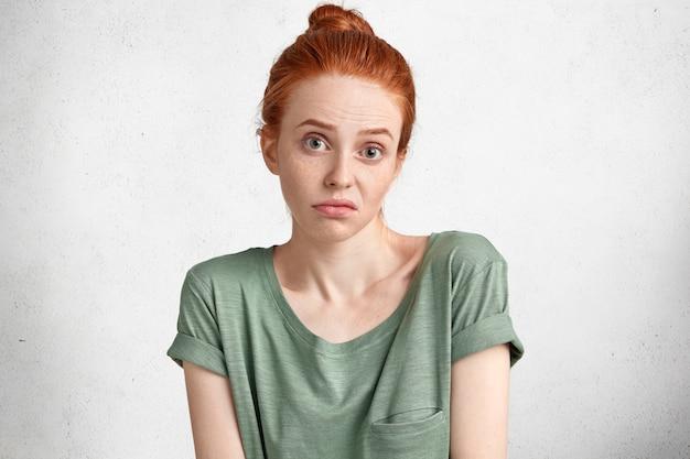 Ujęcie niezadowolonej niepewnej kobiety z rudymi włosami związanymi w kok, wahająca się przed czymś, niezadowolona ze wszystkiego, co stawia na biało