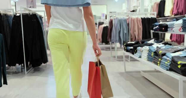 Ujęcie nogi młodej kobiety spaceru z torby na zakupy, choć sklep odzieżowy.