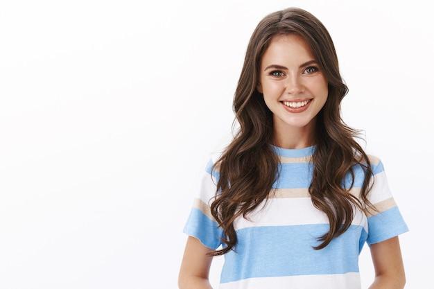 Ujęcie od pasa do góry przyjemna przyjazna nowoczesna dobrze wyglądająca brunetka gotowa pomoc klientka udziela porady, uśmiecha się radośnie wygląda na szczerą i radosną, stoi ambitna i zdeterminowana biała ściana