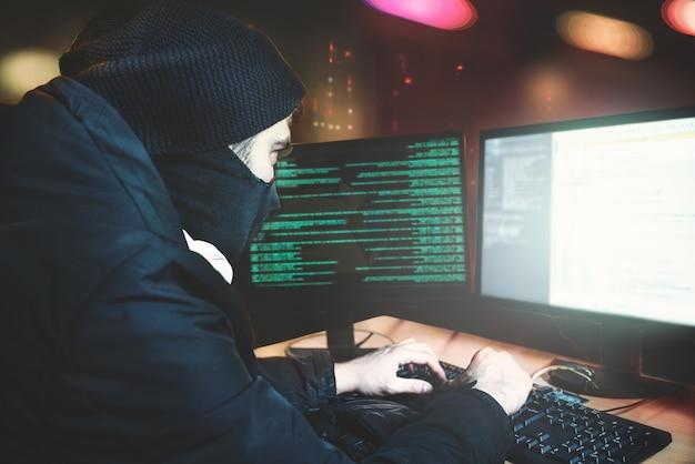 Ujęcie od tyłu do hakera włamującego się do korporacyjnych serwerów danych ze swojej podziemnej kryjówki. miejsce ma ciemną atmosferę, wiele wyświetlaczy