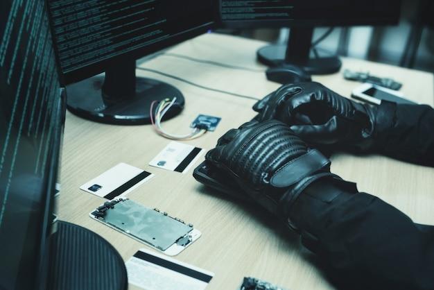 Ujęcie od tyłu do hakera włamującego się do korporacyjnych serwerów danych ze swojej podziemnej kryjówki. widok z bliska rąk hakerów
