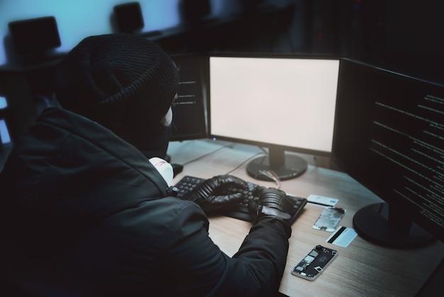 Ujęcie od tyłu do zakapturzonego hakera włamującego się do firmowych serwerów danych ze swojej podziemnej kryjówki. miejsce ma ciemną atmosferę, wiele wyświetlaczy