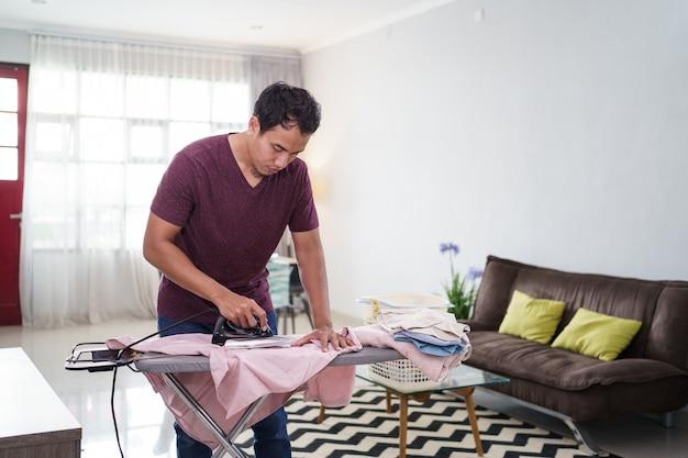 Ujęcie odpowiedzialnego męża lub samotnego mężczyzny zajętego pracami domowymi, rano prasuje koszulę na biurku do prasowania przed pracą,