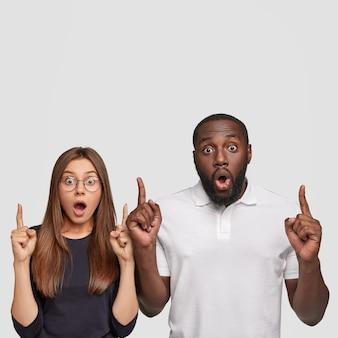 Ujęcie ogłupiałej, emocjonalnej dziewczyny i chłopaka z mieszanej rasy, z oboma palcami wskazującymi do góry