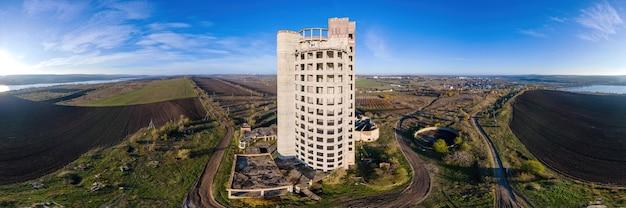 Ujęcie panoramiczne niedokończonego i opuszczonego budynku z drona. naturalny krajobraz mołdawii z polami i drogami wiejskimi