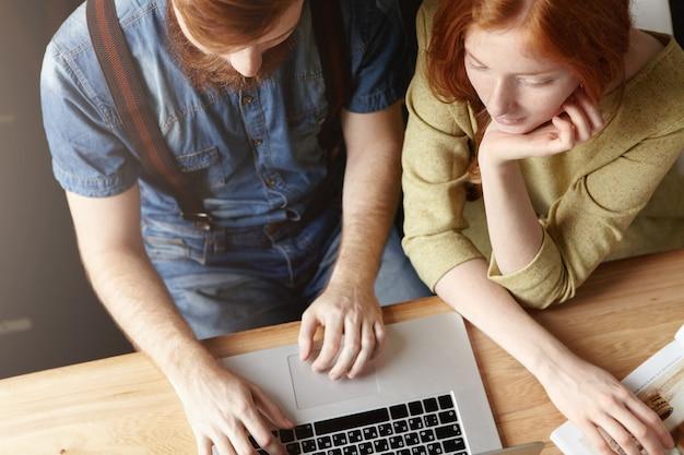 Ujęcie pary za pomocą laptopa siedząc w domu lub kawiarni.
