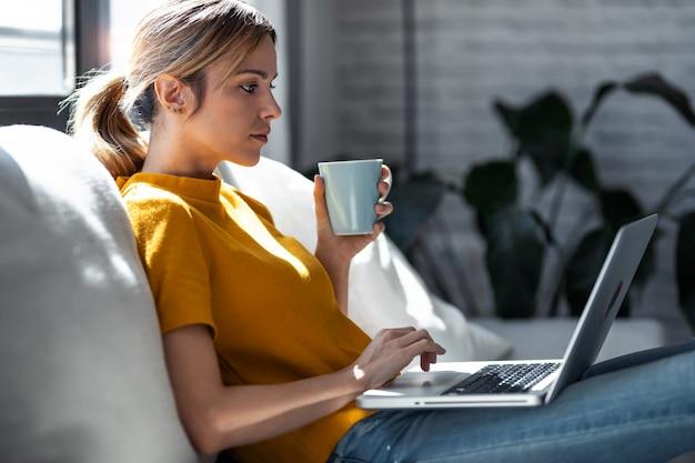 Ujęcie pewnej młodej kobiety pracującej z laptopem podczas picia filiżanki kawy siedzącej na kanapie w domu