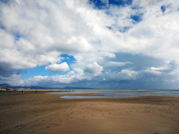 Ujęcie piaszczystej plaży z kilkoma ludzkimi sylwetkami na fuerteventurze w hiszpanii.