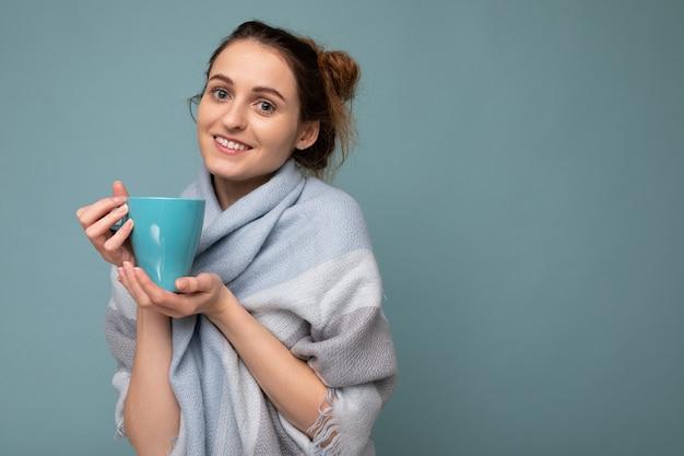 Ujęcie piękna młoda szczęśliwa uśmiechnięta brunetka ubrana w ciepły niebieski szalik na białym tle nad niebieskim