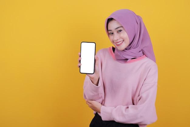 Ujęcie pięknej, atrakcyjnej kobiety, która trzyma w ręku nowoczesny telefon komórkowy, reklamuje nowy ulubiony gadżet