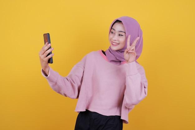 Ujęcie pięknej, atrakcyjnej kobiety trzymającej w ręku nowoczesny telefon komórkowy, reklamującej nowy ulubiony gadżet, zrób zdjęcie