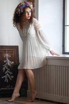 Ujęcie pięknej brunetki z luźnymi włosami otwierającymi drzwi balkonu i wchodzącą na słoneczny taras.
