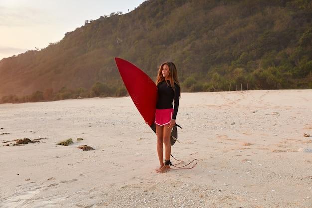 Ujęcie pięknej dziewczyny sprawny w wodoodporne ubrania do surfowania