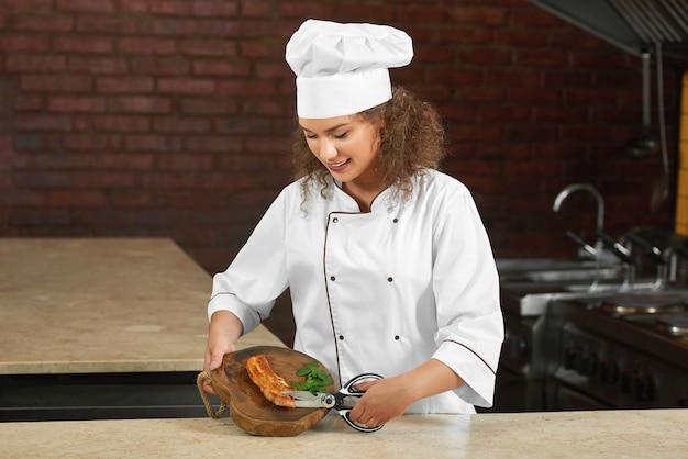 Ujęcie pięknej kobiety kucharz uśmiecha się radośnie podczas pracy w swojej kuchni cięcia mięsa z grilla nożyczkami.