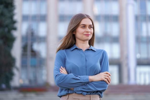Ujęcie pięknej młodej bizneswoman na sobie niebieską koszulę z szyfonu, stojąc na budynku na ulicy z założonymi rękami.