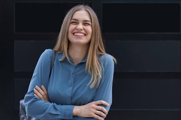 Ujęcie pięknej młodej bizneswoman na sobie niebieską koszulę z szyfonu stojąc z założonymi rękami na czarnej ścianie