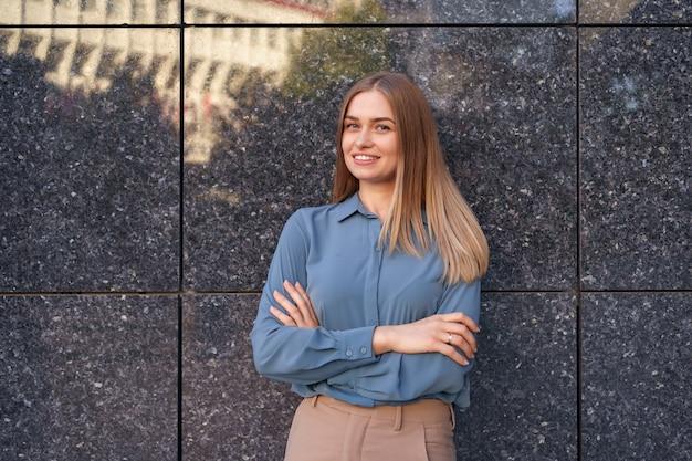 Ujęcie pięknej młodej bizneswoman na sobie niebieską koszulę z szyfonu, stojąc z założonymi rękami na szarej marmurowej ścianie