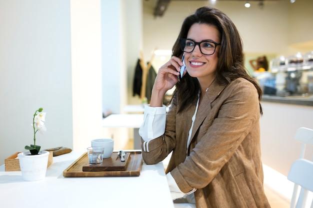 Ujęcie pięknej młodej bizneswoman z okularami rozmawiając z jej telefonem komórkowym w kawiarni.