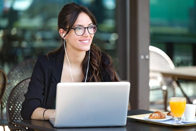 Ujęcie pięknej młodej kobiety patrzącej w bok podczas pracy z laptopem w kawiarni.