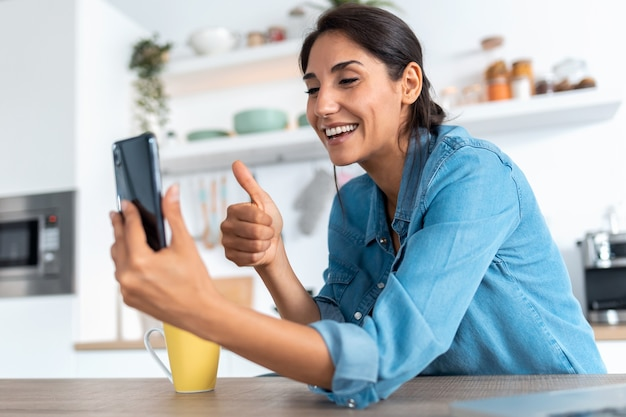 Ujęcie pięknej młodej kobiety podczas rozmowy wideo i pokazując kciuk do smartfona podczas porannej kawy w domu.