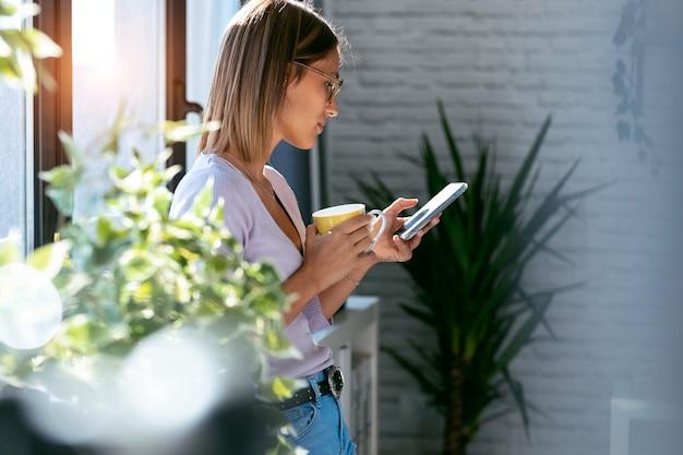 Ujęcie pięknej młodej kobiety za pomocą telefonu komórkowego podczas picia filiżanki kawy stojącej przy oknie w domu.
