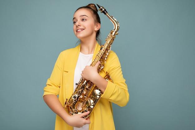Ujęcie pięknej słodkiej szczęśliwej uśmiechniętej brunetki kobiecej nastolatka noszącej modną żółtą kurtkę stojącą