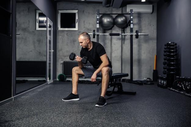 Ujęcie pleców mężczyzny w średnim wieku trzymającego i podnoszącego hantle jedną ręką, siedząc na ławce sportowej w nowoczesnej siłowni