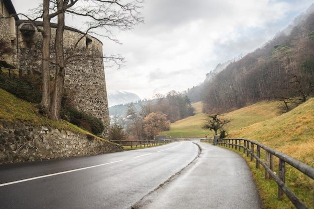 Ujęcie pod dużym kątem drogi prowadzącej w dół ze wzgórza obok zamku vaduz w liechtensteinie