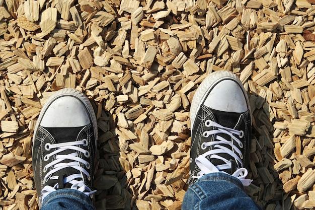 Ujęcie pod dużym kątem przedstawiające stopy osoby stojącej na ziemi pokrytej kawałkami drewna