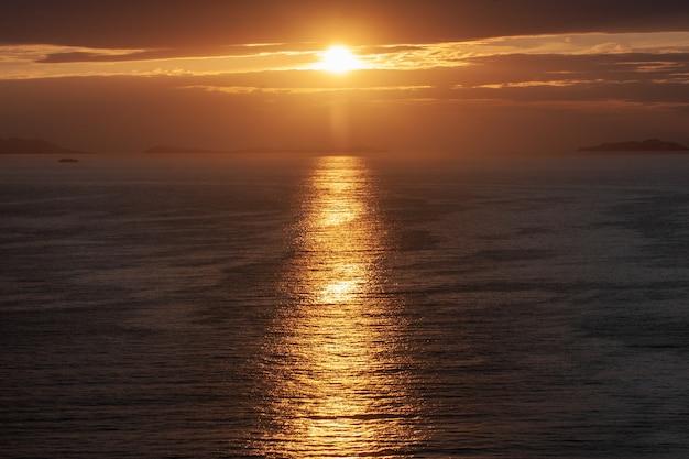 Ujęcie pod dużym kątem słońca świecącego zza chmur, odbijającego się od morza