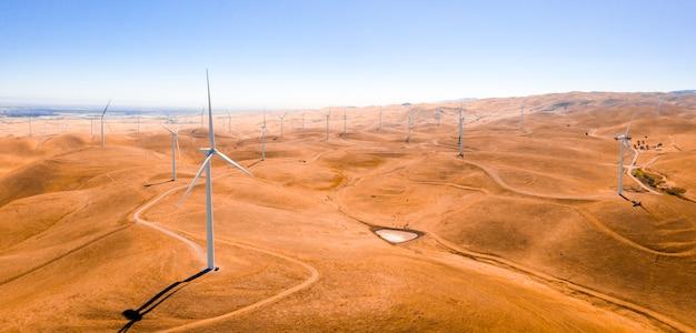 Ujęcie pod dużym kątem turbin wiatrowych na piaszczystym polu uchwycone w słoneczny dzień