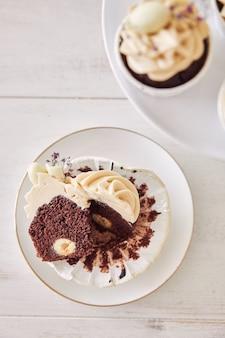 Ujęcie pod wysokim kątem pysznej czekoladowej babeczki z białą polewą śmietankową