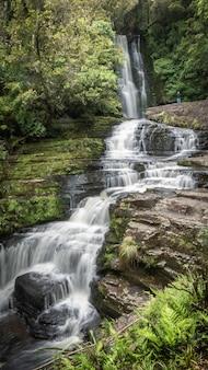 Ujęcie portretowe dużego wodospadu kaskadowego w środku lasu catlins nowa zelandia