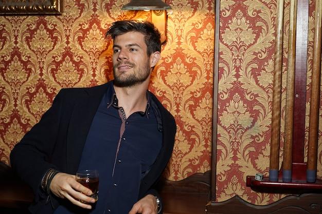 Ujęcie portretowe inteligentnego biznesmena trzymającego whisky w dłoni i uśmiechającego się pewnie