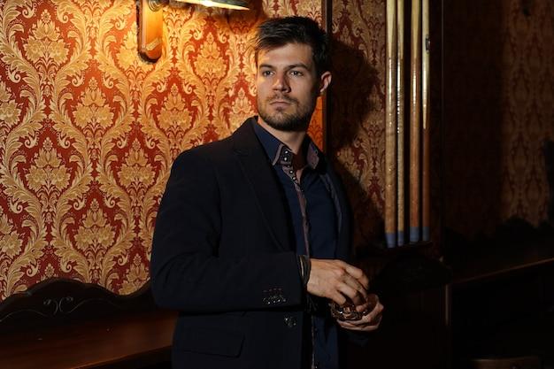Ujęcie portretowe inteligentnego biznesmena trzymającego whisky w dłoniach