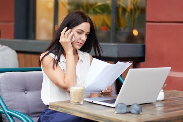 Ujęcie poważnej kobiety-przedsiębiorcy, prowadzi rozmowę przez telefon komórkowy, studiuje dokumenty, używa laptopa do pracy, jest podłączony do bezprzewodowego internetu, siedzi w kawiarni na świeżym powietrzu.