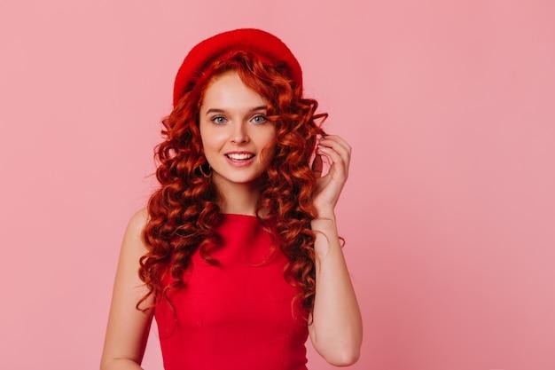 Ujęcie pozytywnej pani z niebieskimi oczami i czerwonymi lokami na różowej przestrzeni. dziewczyna w jasnym nakryciu głowy i czerwonej górze patrząc na kamery.