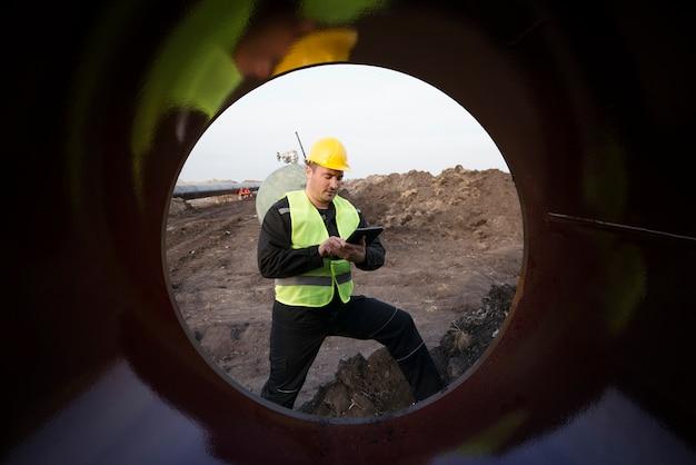 Ujęcie pracownika pola naftowego sprawdzającego jakość rur gazowych na placu budowy