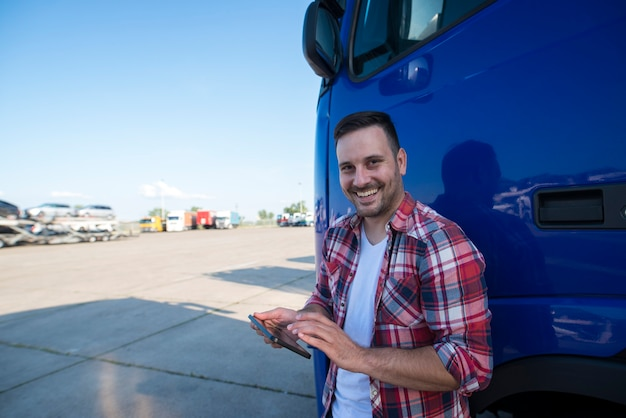 Ujęcie profesjonalnego kierowcy ciężarówki stojącego przy swoim samochodzie z tabletem i konfigurującego nawigację gps do następnej jazdy