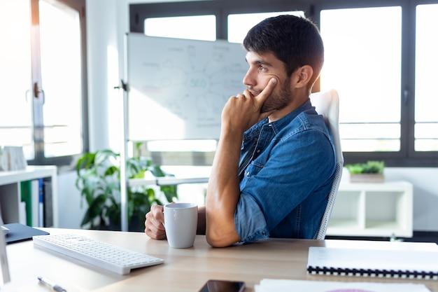 Ujęcie programisty myślącego o nowym projekcie podczas pracy z komputerem w nowoczesnym biurze startowym.