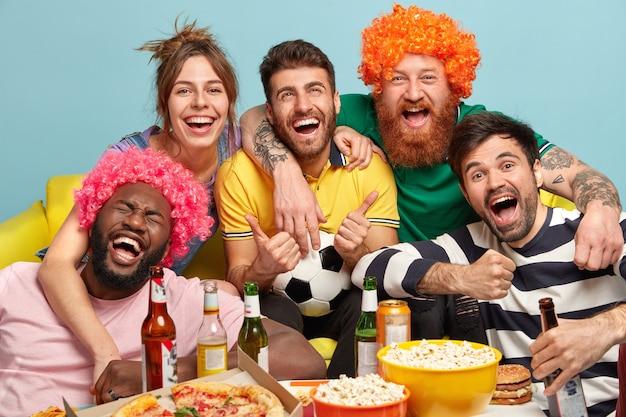 Ujęcie przyjaznych towarzyszy obejmujących się i uśmiechających się radośnie, kibicować zwycięskiej ulubionej drużynie, miło spędzać czas, oglądając ekscytujący mecz piłki nożnej, pijąc piwo i jedząc fast food. śmieszne wsparcie fanów